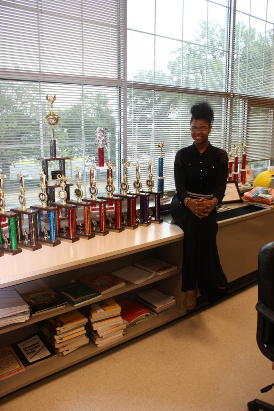Middle College debate varsity member Alexis Nicole Thornton shows off the many trophies the team has earned.  She has been a member since since her sophomore year. By Eboni Johnson
