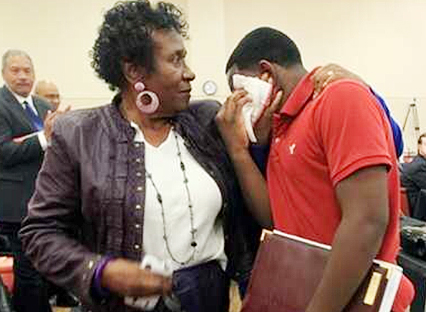 Photo courtesy of Kemario Davis State representative Barbara Cooper comforts Carver student Kemario Davis moments after speaking to the school board in hopes of keeping his school open.
